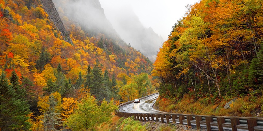Foggy mountains full of fall foliage while a car drives through on an intersecting road at the Moose Path Trail
