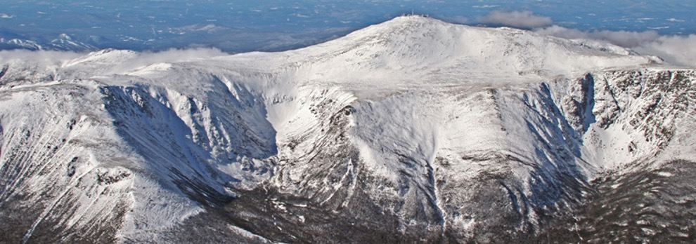 View from the summit of Mount Washington covered in snow on a sunny day
