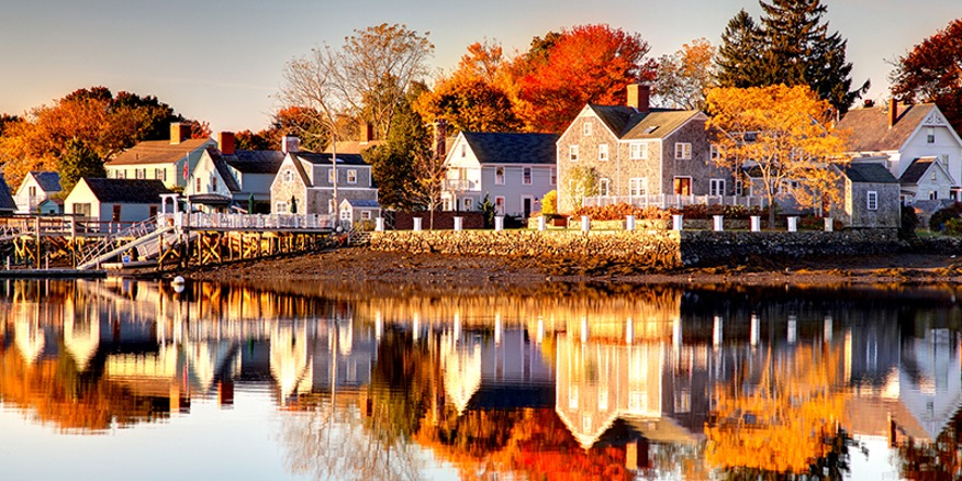 Line of homes along the waters edge and fall foliage all around at American Independence Byway