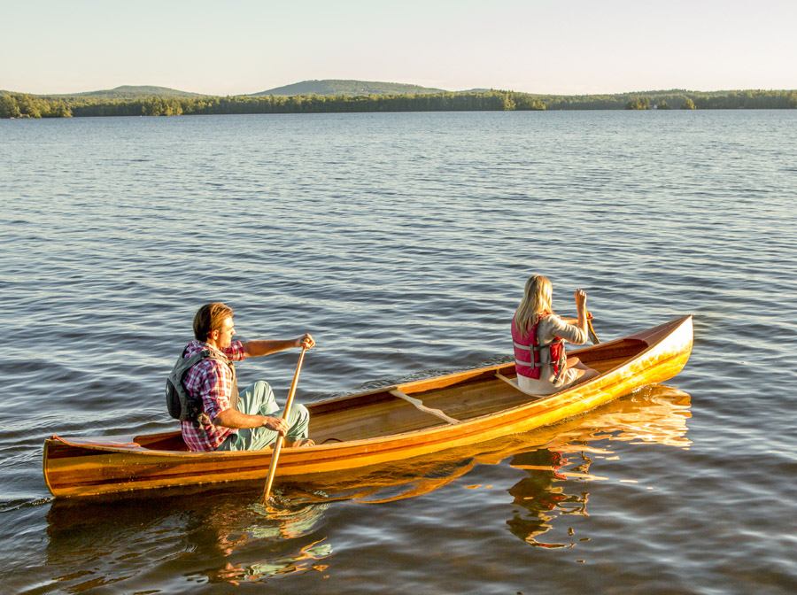 a man and woman paddling a canoe on a lake