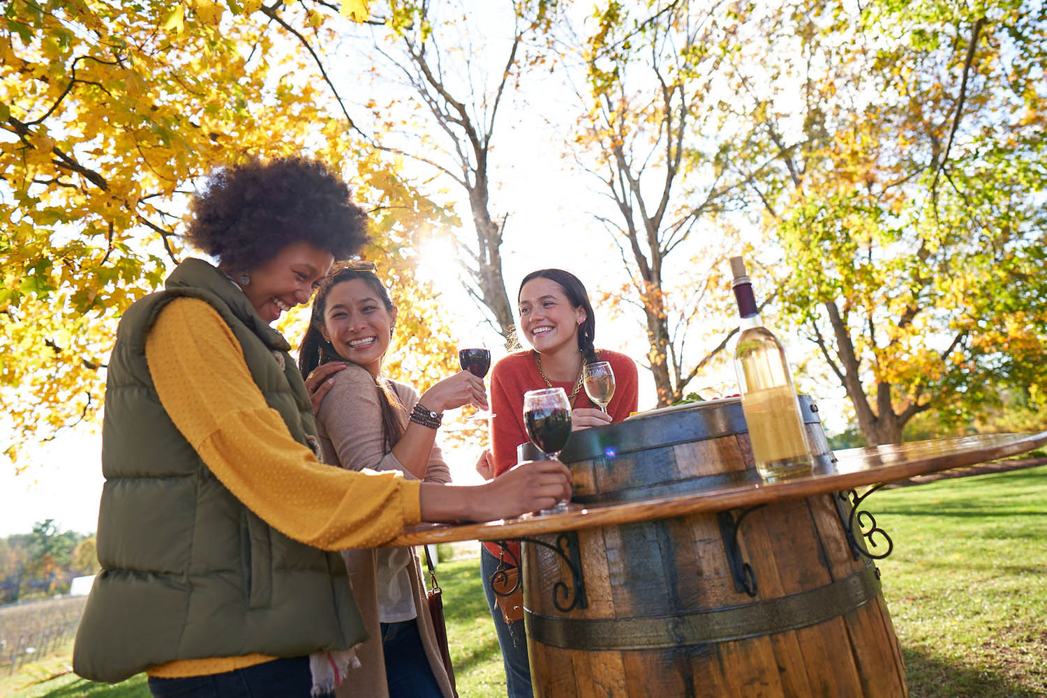 Woman outdoors gathered around a table wine tasting