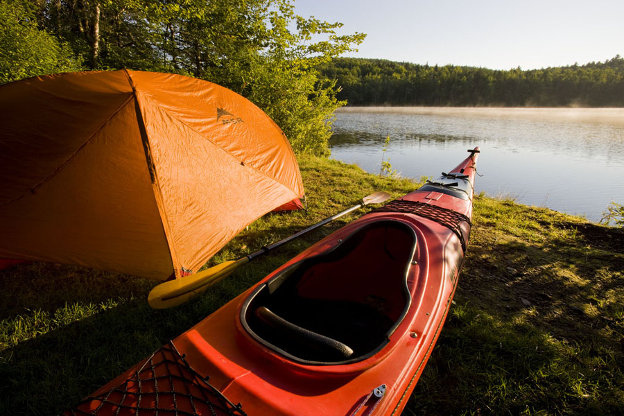 Tent and kayak by river