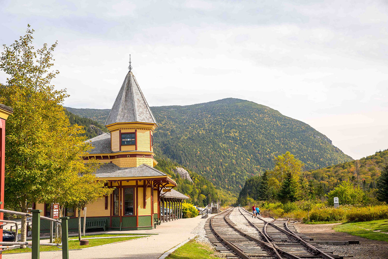 Railway station surrounded by mountains and foliage