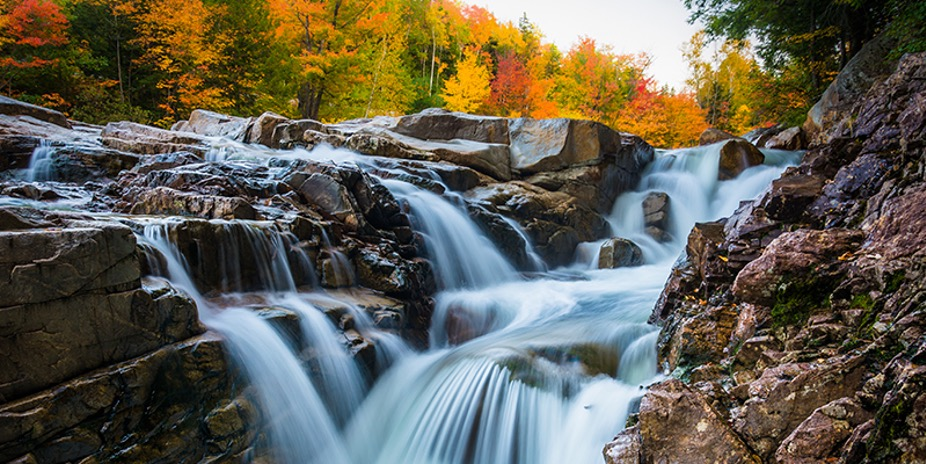 Image of small waterfalls on The White Mountain Trail with fall foliage in the background