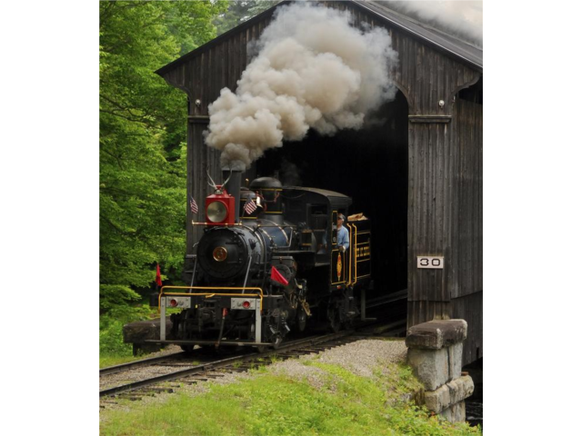 1920 Climax locomotive steaming through authentic railroad covered bridge